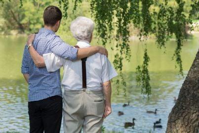 figlio abbraccia il proprio padre anziano
