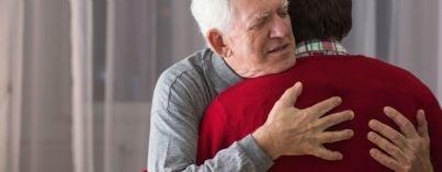 figlio abbraccia padre anziano