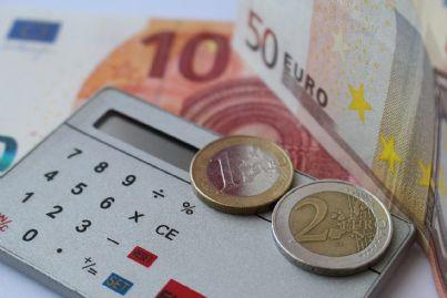 Calcolatrice adagiata su uno sfondo di soldi