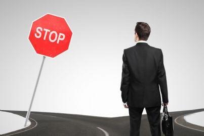 uomo incontro a un bivio deve fermarsi per stop