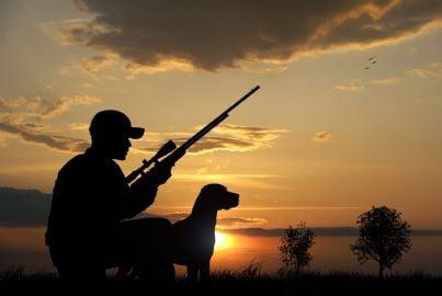 uomo con fucile da caccia e cane
