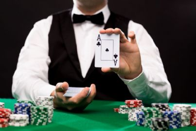 uomo al tavolo da gioco mostra carte