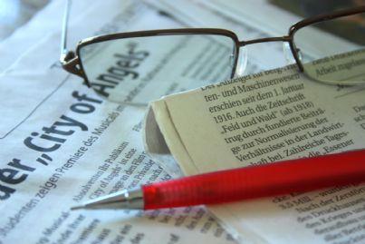 Giornali penna e occhiali su una scrivania