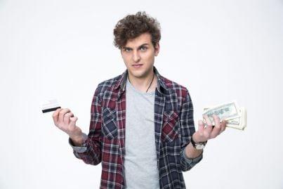 ragazzo con contante in mano indeciso se usare carta di credito