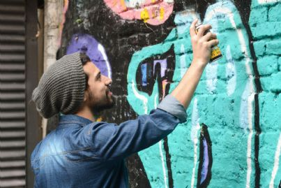 writer che fa graffiti su un muro