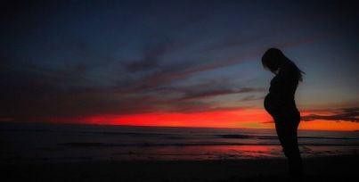 Donna in stato interessante su una spiaggia al tramonto