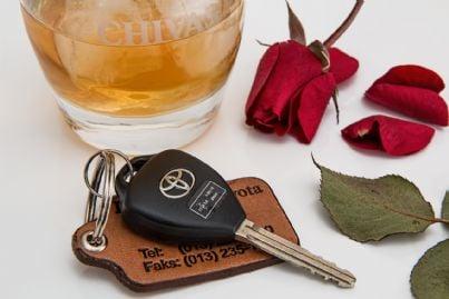 Guida in stato di ebrezza rappresentata da un bicchiere di liquore accanto a delle chiavi di un'auto