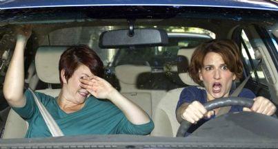 donna alla guida spericolata con passeggero spaventato
