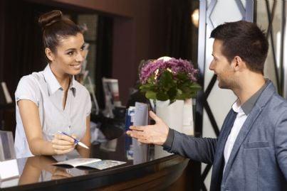 cliente e receptionist dialogano in albergo