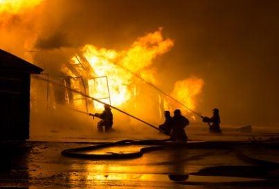 Incendio e pompieri che tentano di domarlo