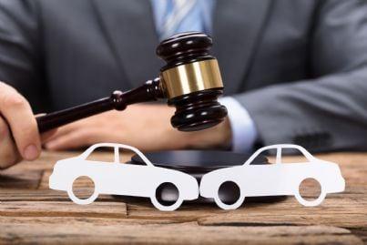 giudice con martello e macchina per incidente stradale