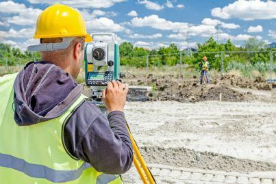 ingegnere che prende misure terreno in costruzione