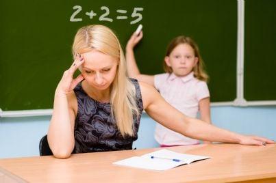 insegnante disperata di fronte a bambina asino alla lavagna