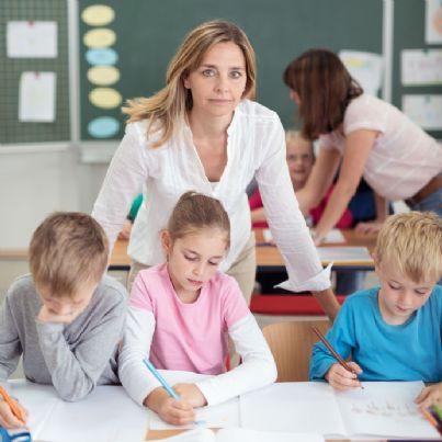 insegnante seria in mezzo agli alunni di scuola elementare