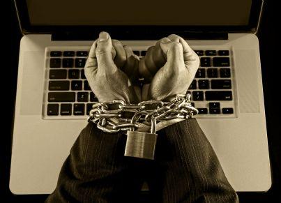 mani ammanettate di fronte a un pc concetto niente comunicazione carcere
