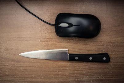 coltello vicino a pc e mouse concetto violenza della rete