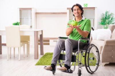 giovane invalido su sedia a rotelle con salvadanaio
