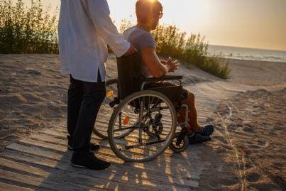 uomo assiste invalido sulla sedia a rotelle