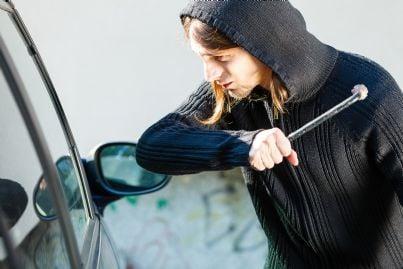 un uomo che cerca di rubare una macchina