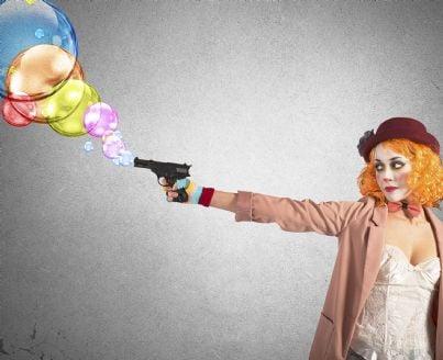 ladro vestito da clown con pistola giocattolo sparabolle