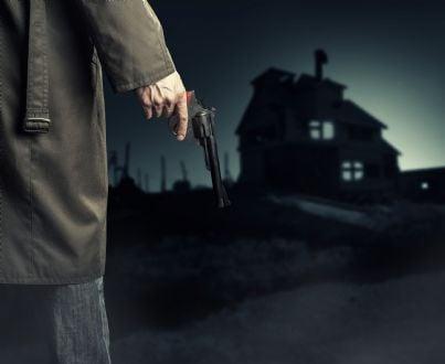 ladro che si dirige di notte verso una casa con pistola in mano