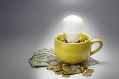 lampadina dentro tazza piena di soldi