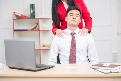donna che massaggio collo uomo in ufficio