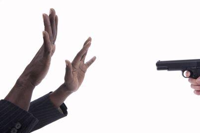 uomo punta pistola ad altro con mani alzate