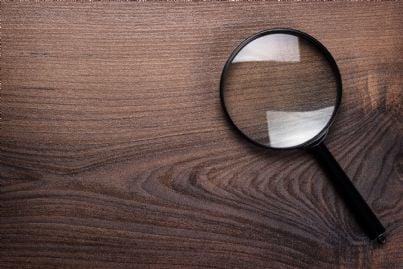 lente di ingrandimento su sfondo marrone