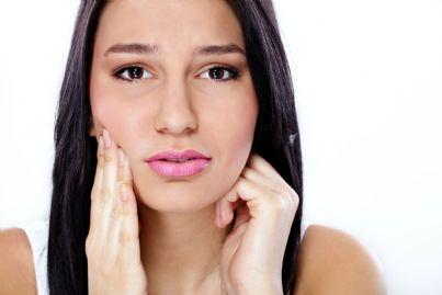 donna che tocca viso concetto lesione