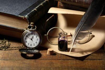 Scrivania con penna, libri e orologio