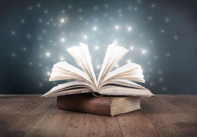 libro aperto sul tavolo e sfondo di stelle