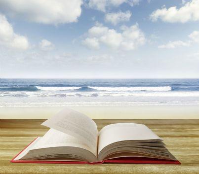 libro sulla spiaggia con mare sullo sfondo