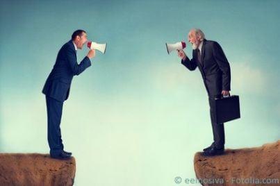 Due persone che litigano usando ciascuno un megafono