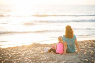 Madre e figlia sedute sulla spiaggia