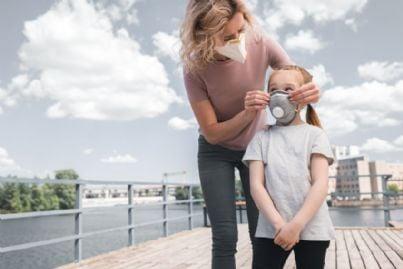 madre fa indossare mascherina alla figlia