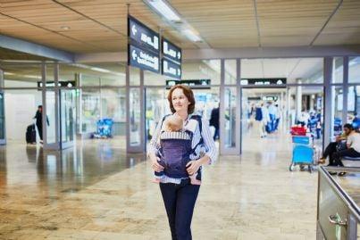 madre con neonato in braccio in aeroporto