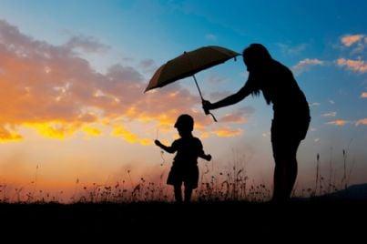 madre tutela figlio con ombrello al tramonto mentre gioca