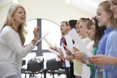 maestra che insegna ai bambini a cantare