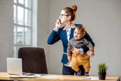 mamma che lavora al telefono con il figlio in braccio