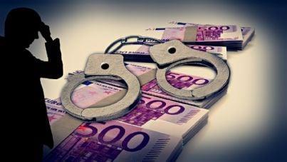 Uomo guarda manette appoggiate su pila di euro