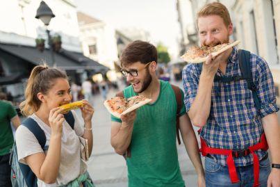 ragazzi che mangiano pizza per strada