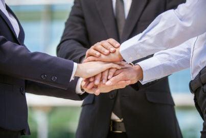 uomini affari con mani una su altra per accordo raggiunto