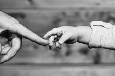 mano di un bambino che si unisce a quella del padre