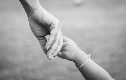 mano della madre che stringe quella del bambino per sostenerlo
