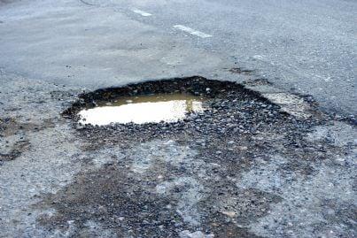 buca su asfalto marciapiede