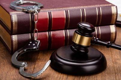 martello del giudice e manette su un libro di diritto