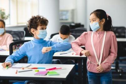 bambini indossano mascherina covid a scuola