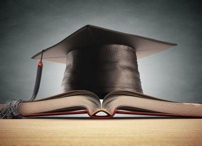 cappello di laurea sopra pila di libri