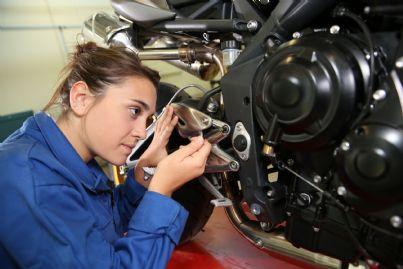 donna meccanico al lavoro ripara moto